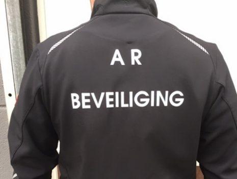Man met zwarte jas opschrift achterkant van de jas de tekst A.R. Beveiliging